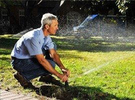 irrigation technician inspecting and adjusting a sprinkler head