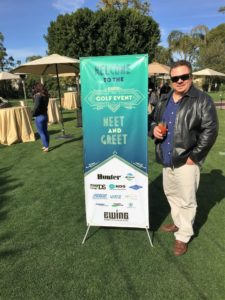 Thomas Zullo next to a golf event sign